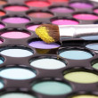Brush in yellow on make-up palette - Stock Photo