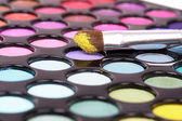 Brush in yellow on make-up palette — Stock Photo