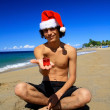 Santa Claus with gift  on beach — Stockfoto