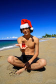 Santa Claus with gift on beach — Foto Stock