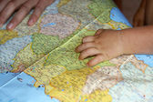 Child's hand on a map — Stock Photo