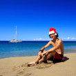 Handsome Santa Claus sitting on beach — Stock Photo