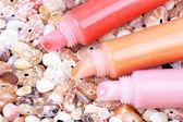 Three lip gloss tubes on cockleshells — Stock Photo