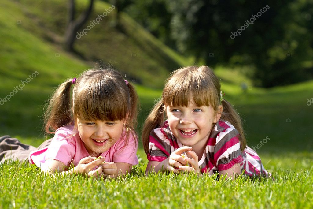 Two little smiling girls lying on the grass in the park — Stok fotoğraf #1036802