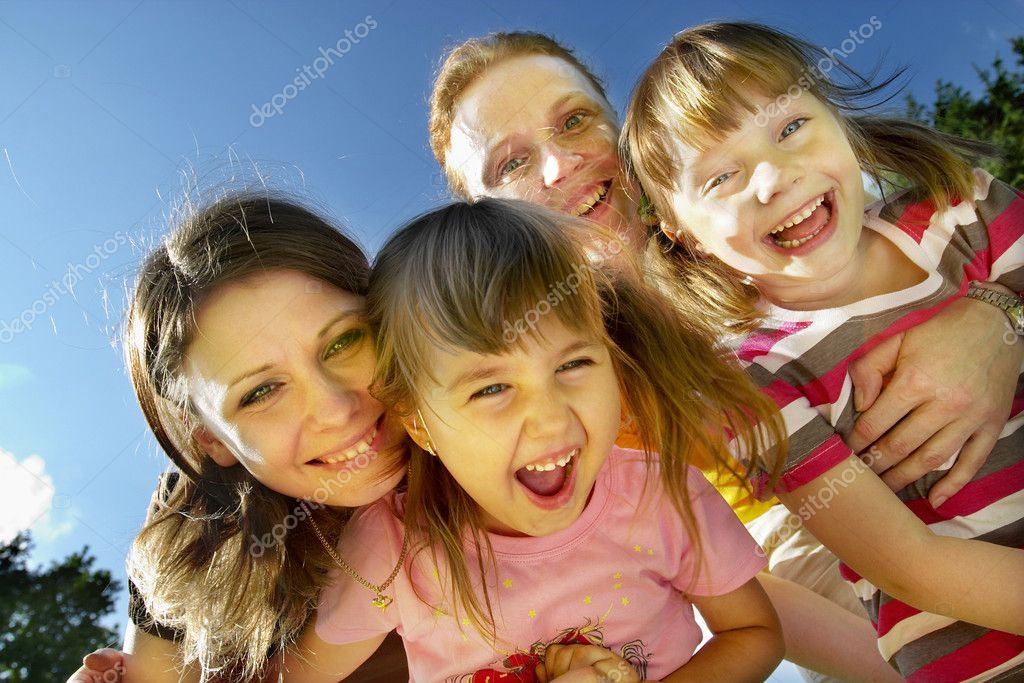 Two mothers with their little daughters smiling and laughing in the park — Stock Photo #1036803