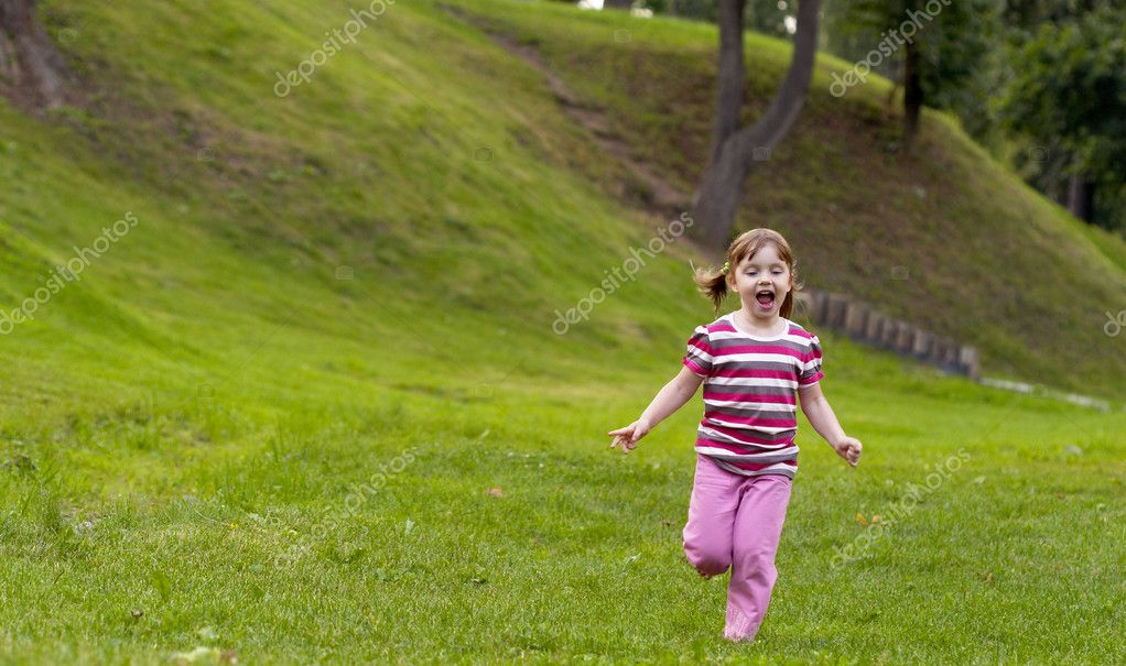 Little girl running on the grass in the park — Stock Photo #1082587