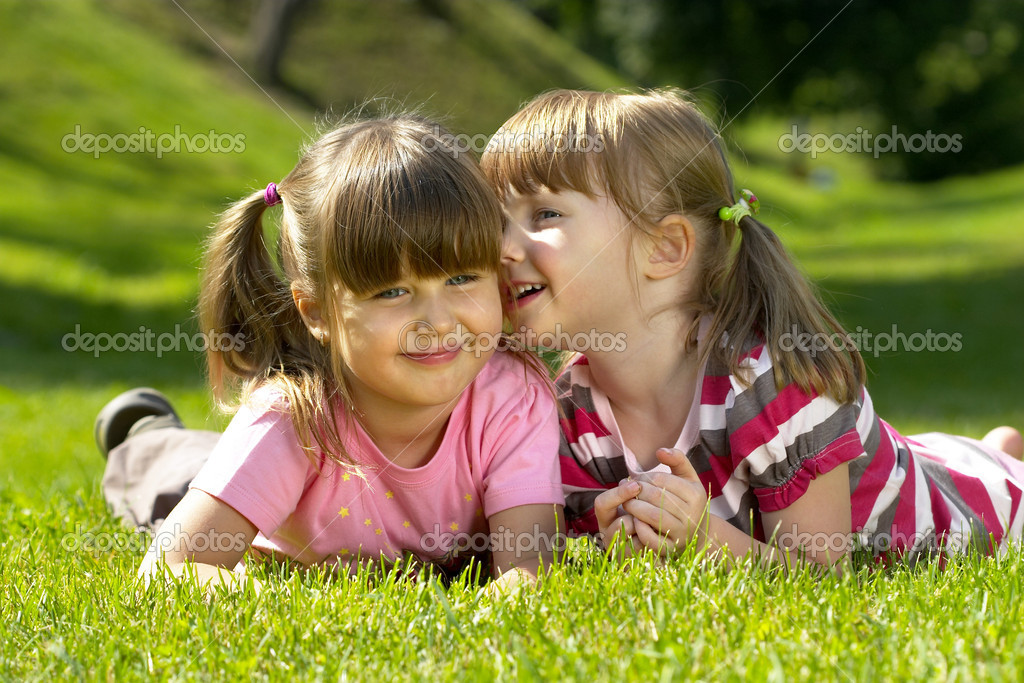 Two little girl lying on the grass in the park. One whispering a secret to another. — Foto de Stock   #1082632