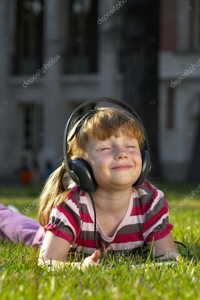 Little girl lying on the grass in the park, listening the music  Stock Photo #1082648