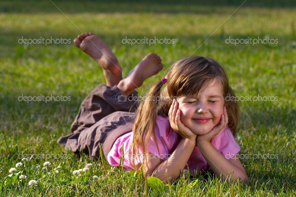 Little girl lying on the grass in the park, dreaming of something — Stock Photo #1082655