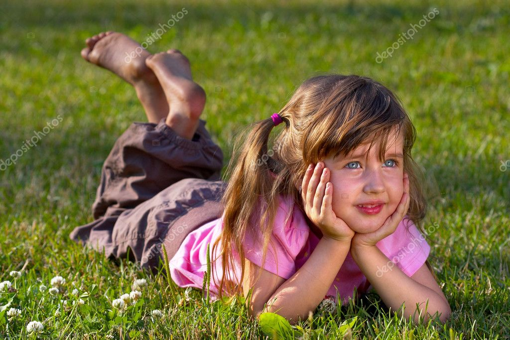 Little girl lying on the grass in the park, dreaming of something — Stock Photo #1082659
