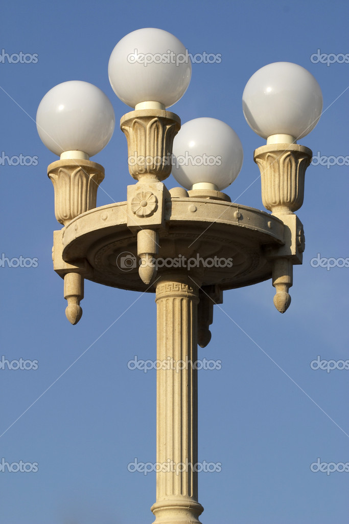 Beautiful street lamp with four matte glass balls over clear blue sky — Stock Photo #1085149