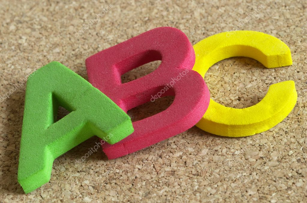 3D Plastic ABC letters over cork desk background macro shot — Stock Photo #1085449