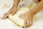 Hands of the child knead the dough for a — Stock Photo