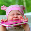 Baby eating book — Stock Photo