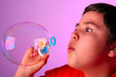 Young boy blowing soap bubbles — Stock Photo