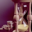 Sand clock and coins — Stock Photo