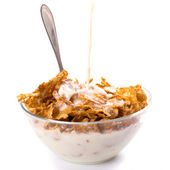 Milk pouring onto cornflakes isolated on white — Stock Photo