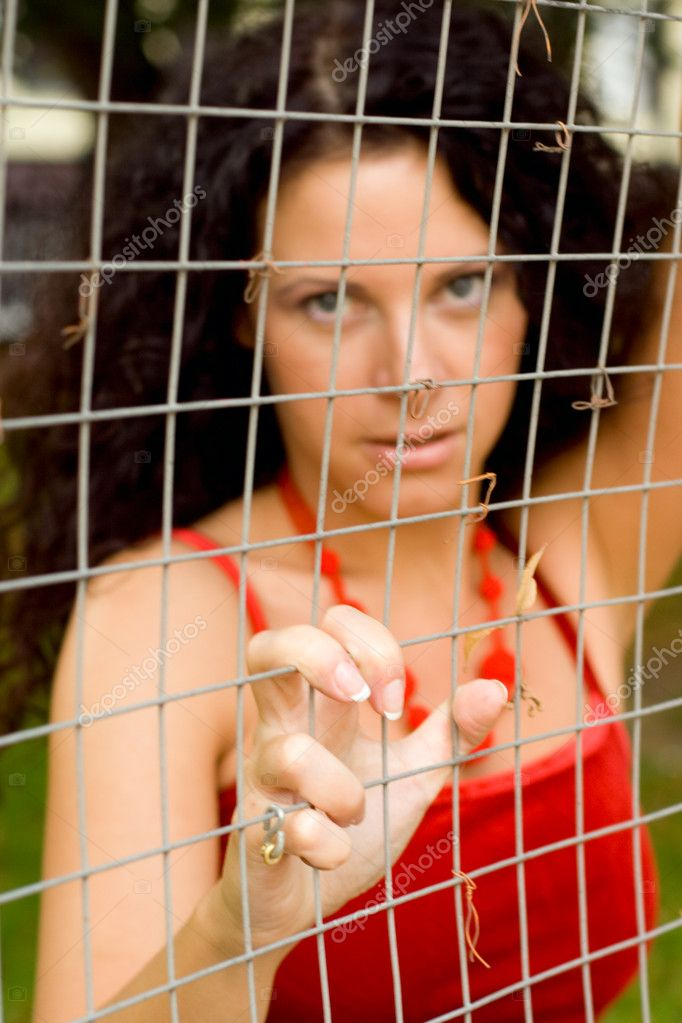 Beautiful woman behind a lattice. focus on hand.  Stock Photo #1069853