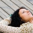 Stock Photo: Woman lying on wooden floor