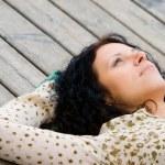 Woman lying on wooden floor — Stock Photo