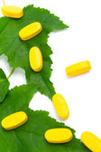 Vitamin pills over green leaves — Stock Photo