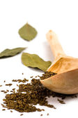 Cumin on wooden spoon and bay leaves — Stock Photo