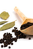 Pepper on wooden spoon and bay leaves — Stock Photo