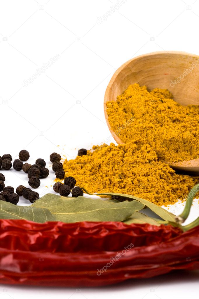 Spices: curry in wooden spoon, pepper, pimento, and bay leaves on white background — Stock Photo #2258711