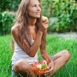 Beautiful woman eating pear on the grass — Stock Photo