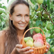 Beautiful lady in the garden with apples — Stock Photo