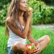 Beautiful lady eating pear on grass — Stock Photo
