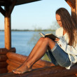 Young woman reading book in summerhouse — Stock Photo