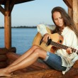 Foto Stock: Young womplaying guitar in summerhous