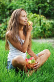 Beautiful lady eating pear on grass — Foto de Stock