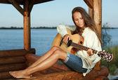 Mladá žena hraje na kytaru v summerhous — Stock fotografie