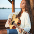 Young woman playing guitar in summerhous - Stock Photo