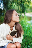 Thoughtful Young lady with book near the — Stock Photo