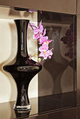 Vase with orchid flower in brown niche — Stock Photo