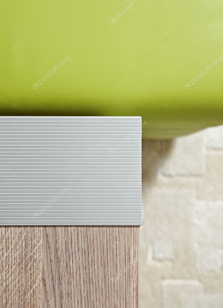 Aluminium bedside-table corner and green leather sofa fragments — Stock Photo #1055665