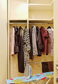 Wardrobe with clothes and ironing board — Stock Photo