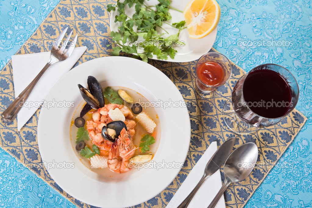 Seafood soup with shrimps and mussels on blue ornate table-cloth  Stock Photo #1061551