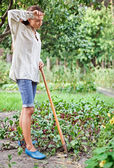 Tired young woman with hoe working — Photo