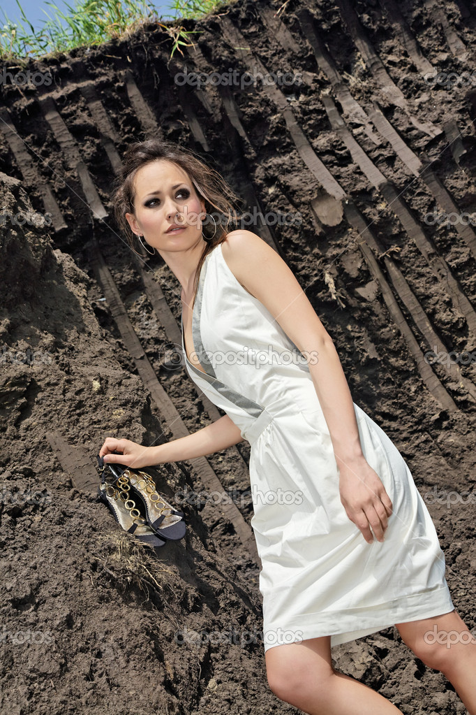 Beautiful brunette in white sundress inside a deep black ground quarry — Stock Photo #1594146