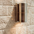 Modern metal lamp on ashlar wall - Stock Photo