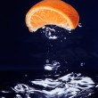 Orange (mandarin) falling in blue water — Stock Photo