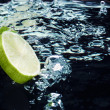 Royalty-Free Stock Photo: Slice of lime (lemon)  falling in water