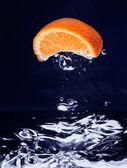 Orange (mandarin) falling in blue water — Stock Photo