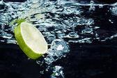 Slice of lime (lemon) falling in water — Stock Photo