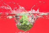 Green broccoli falling in water on red — Stock Photo