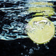 Slice of lime (lemon) falling in water — Stock Photo